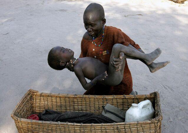 Uma mulher coloca o seu filho, que tem malária, em uma canasta para levá-lo a um hospital dos Médicos sem Fronteiras, no Sudão do Sul em 21 de dezembro de 2005