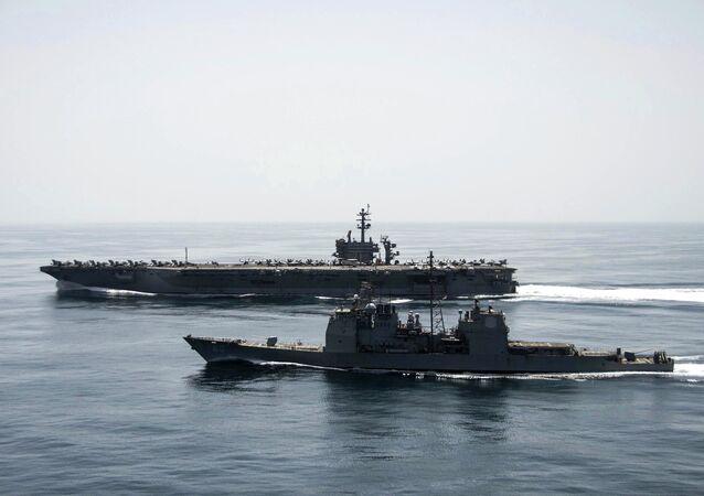 O porta-aviões USS Theodore Roosevelt (CVN 71) e o cruzador de mísseis guiados USS Normandy (CG 60) operam no Mar Arábico realizando operações de segurança marítima. Foto tirada em 21 de abril de 2015.
