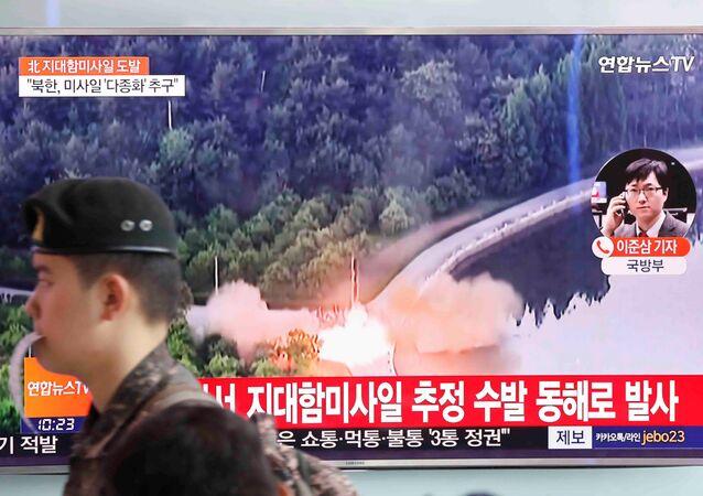 Soldado sul-coreano passa por uma TV que transmite uma reportagem a respeito do mais recente teste com mísseis da Coreia do Norte