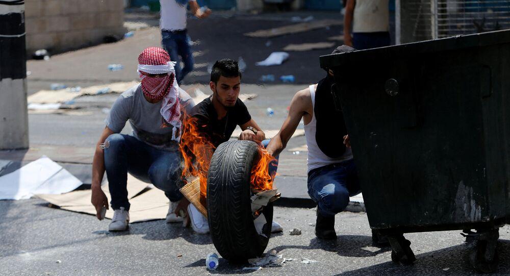 Manifestantes palestinos queimam um pneu em Belém em 21 de julho de 2017; confrontos com polícia começaram após tensão por causa da entrada dificultada ao Monte do Templo