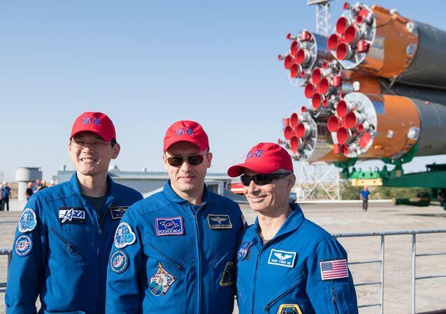 Os membros da equipe de apoio Norishige Kanai da Agência de Exploração Aeroespacial do Japão (JAXA), à esquerda, Alexander Misurkin da Roscosmos, centro e Mark Vande Hei da NASA, à direita, posam para uma foto à medida que a nave espacial Soyuz MS-05 chega à base de lançamento depois de ser retirada do trem no Cosmódromo de Baikonur, no Cazaquistão, na quarta-feira, 26 de julho de 2017.