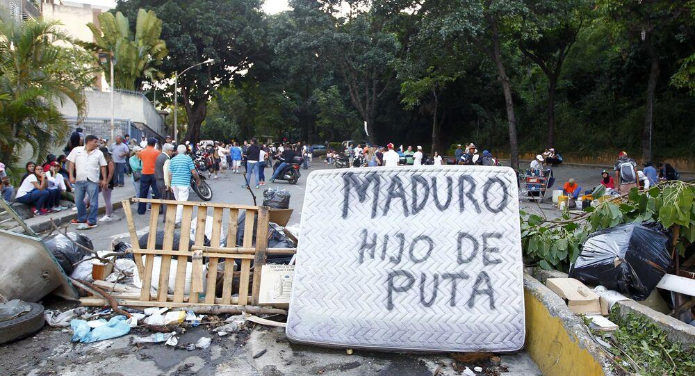 As pessoas passam por uma barricada de rua que inclui um colchão com as palavras Maduro filho da puta durante confrontos nas eleições da Assembleia Constituinte realizadas em Caracas, Venezuela, 30 de julho de 2017.