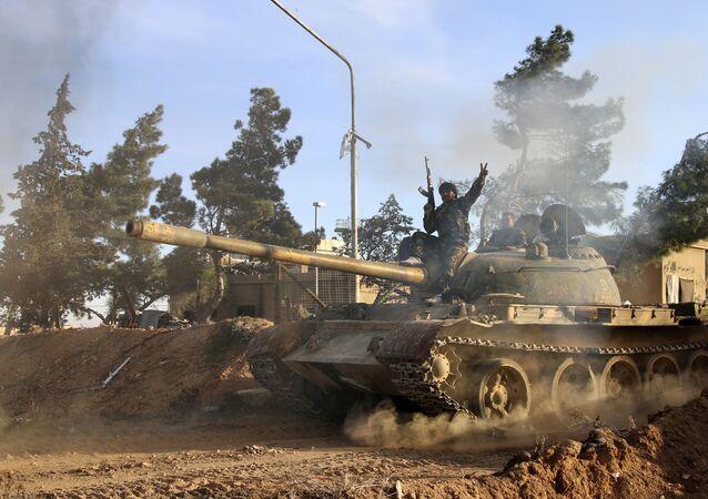 Combatente voluntário das Forças do Governo Sírio em cima de um tanque na província de Raqqa, Síria
