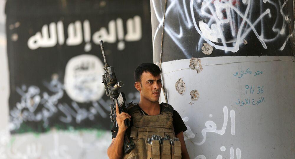 Militar das forças antiterroristas iraquianas perto de um graffiti mostrando o emblema do Daesh, Iraque (foto de arquivo)