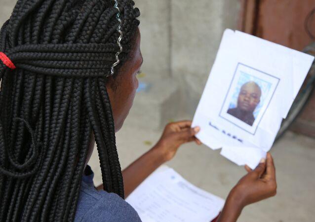 Jacquendia Cangé segura a foto do policial nigeriano da ONU, que ela alega a ter estuprado: 'Nunca vou conseguir perdoar', afirma