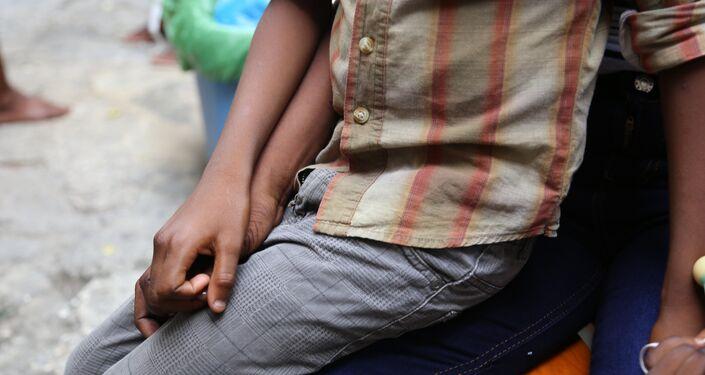 Ashford sentado no colo da mãe, Martine Gestimé. Ela alega que o menino é filho de um brasileiro que a estuprou em 2007.