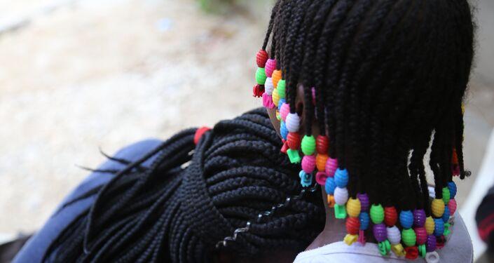 Jacquendia repousa a cabeça sob a filha, que não será identificada a pedido da mãe. Ela seria resultado de um estupro cometido por um nigeriano servindo à UNPOL (Polícia das Nações Unidas)