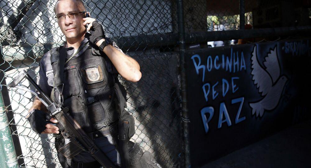Policial militar ao lado de uma mensagem de paz na comunidade da Rocinha, no Rio de Janeiro