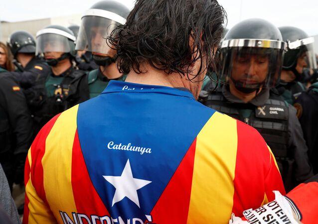 Um homem enfrenta os guardas civis espanhois durante referendo da independência proibida em Sant Julia de Ramis.