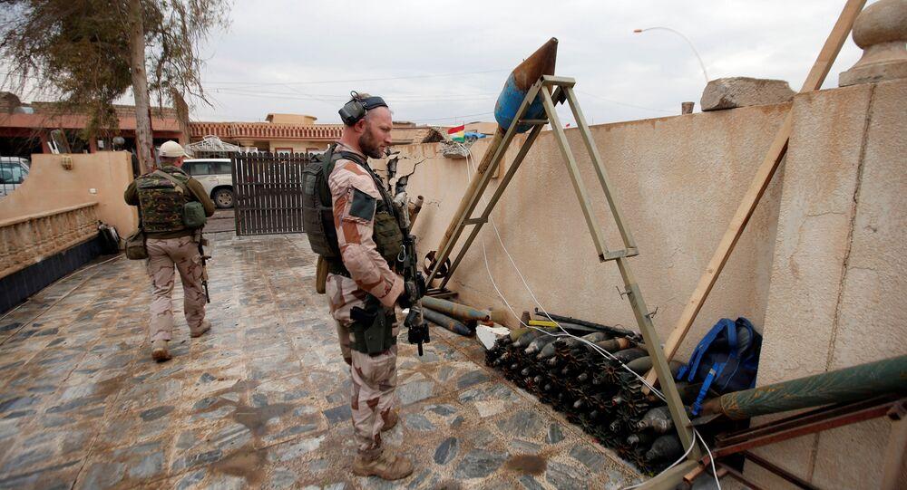 Soldado norte-americano olhando para as armas e as munições do Daesh em Mossul, Iraque