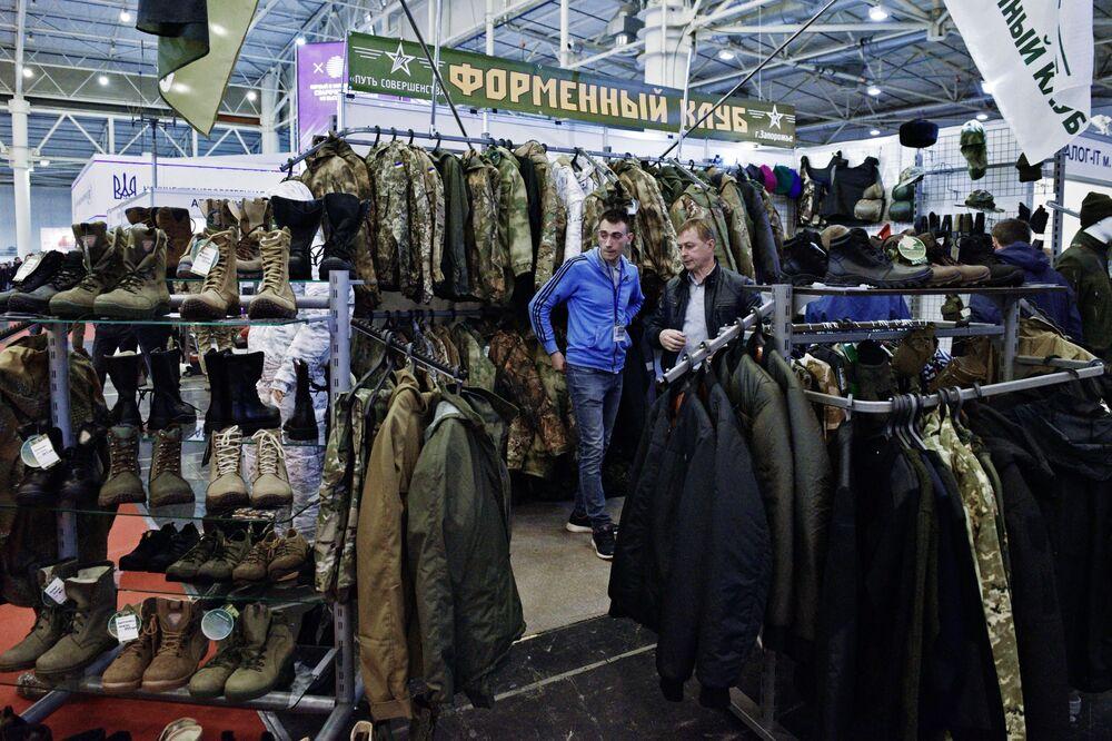 Homens examinam roupa, calçado e uniformes militares durante a exposição Armas e Segurança 2017 em Kiev