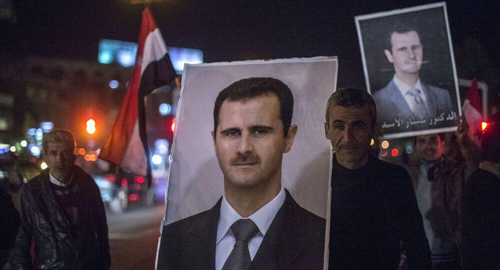 Habitantes de Damasco seguram retratos de Bashar Assad (foto de arquivo)