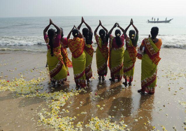Mulheres indianas rezam na praia (imagem ilustrativa)