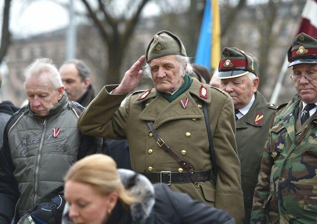 Um homem, vestindo uniforme militar, saúda os veteranos da Legião Letã