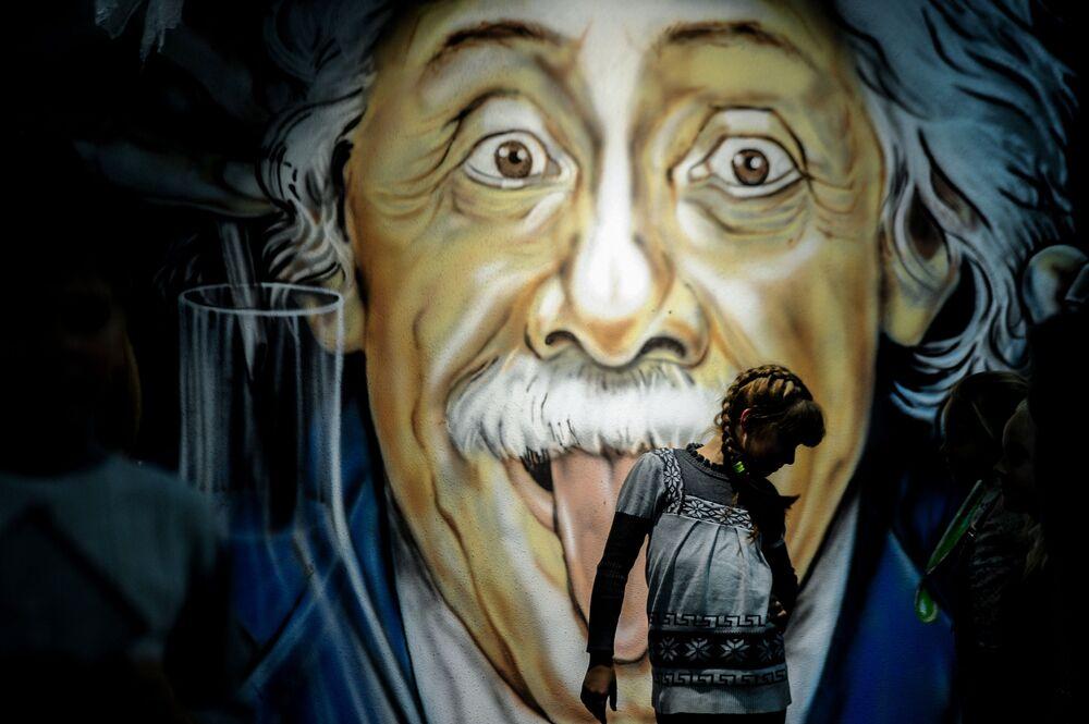 Menina passa em frente de grafite com imagem do físico de origem alemã Albert Einstein, na cidade bielorrussa de Minsk