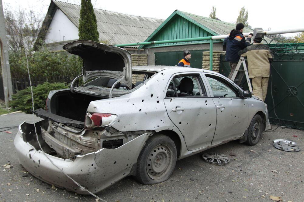 Funcionários dos serviços comunais reparam tubo de gás para aquecimento danificados por tiros noturnos, em Donetsk