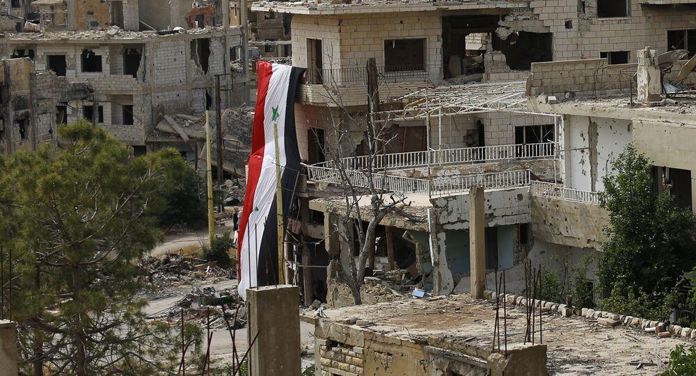 Bandeira nacional da Síria em um edifício danificado na cidade de Al-Zabadani, Síria