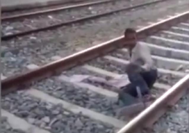 Indiano arrisca própria vida ao atravessar os trilhos