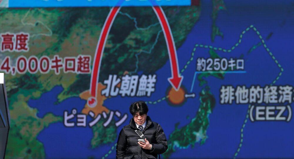 Um jovem passa na frente de uma televisão de rua em Tóquio, Japão, em 29 de novembro de 2017, durante uma transmissão da notícia sobre o lançamento de míssil pela Coreia do Norte