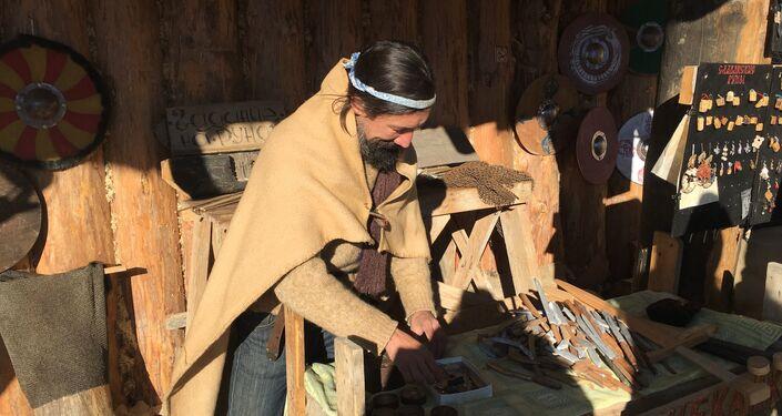 Um dos moradores do parque Viking que se ocupa da fabricação de amuletos com runas, peças militares da época e cunhagem de moedas