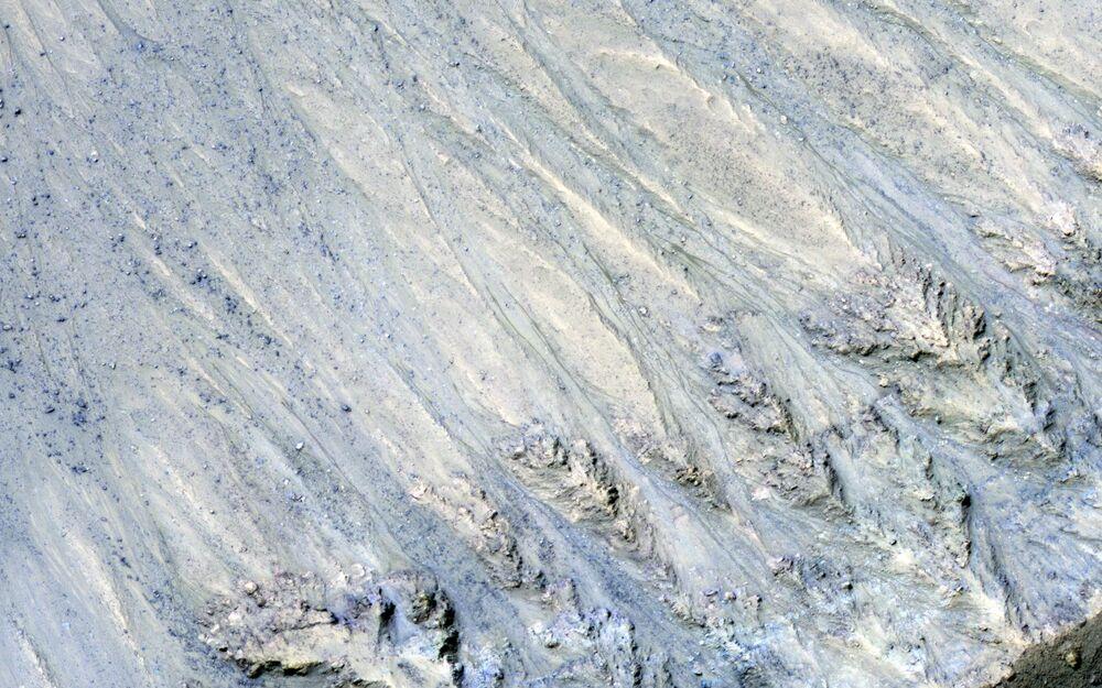 Faixas escuras na superfície marciana que surgiram na sequência do movimento de fluxos de areia seca, capturadas pela sonda da NASA, Mars Reconnaissance Orbiter